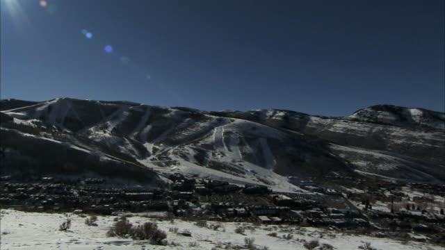 snow mountains w/ ski trails to ski resorts , bright sun glare top of frame, town lower frame. ut - park city utah stock videos & royalty-free footage