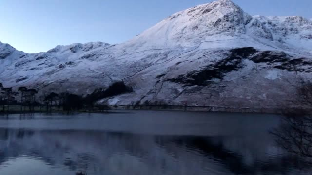 snow on the hills around buttermere in the lake district cumbria after the uk had its coldest night of the winter so far as the cold snap continues... - snow stock videos & royalty-free footage