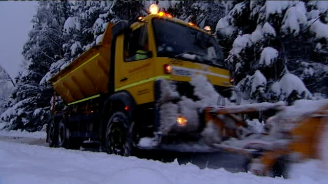 day snow plough along in heavy snow as vehicle slows and wheels spin on road driver clearing snow from beneath snow plough - snow vehicle stock videos and b-roll footage
