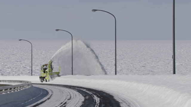Snow plough clears coastal road by blowing snow to one side.