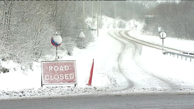 snow ploughs towards on road 'road closed' sign closed refreshment stand surrounded by snow car towards on icy road - road closed sign stock videos & royalty-free footage