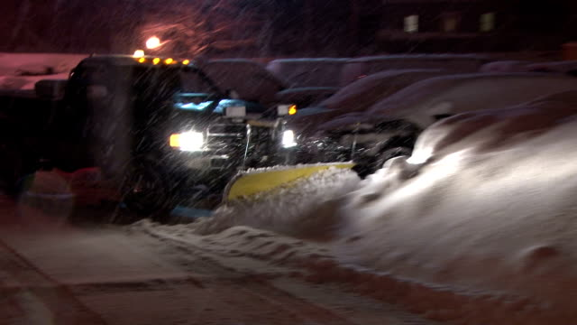 A snow plow clears a parking lot of a hotel as a blizzard takes aim at New England