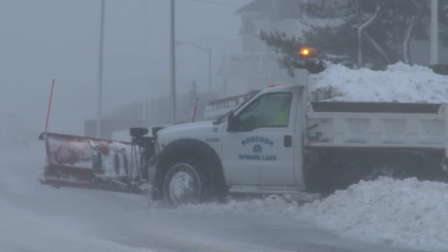 a snow plow clears the road of deep snow along ocean avenue in belmar nj during the height of the blizzard of 2016 - ocean avenue stock videos & royalty-free footage