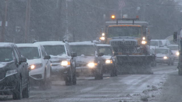 Snow Plow Driving In Traffic During A Snowstorm, Nor'easter
