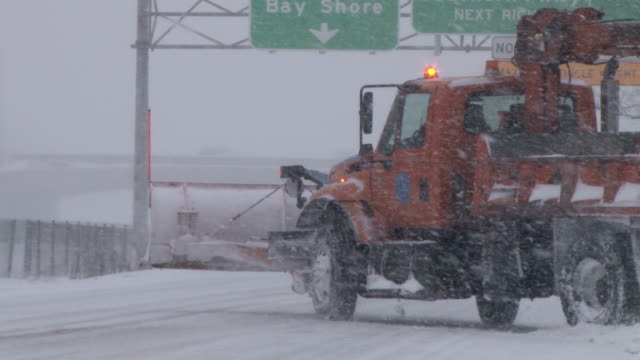 Snow plow pulling on to Sunrise Highway on Long Island during the height of a blizzard