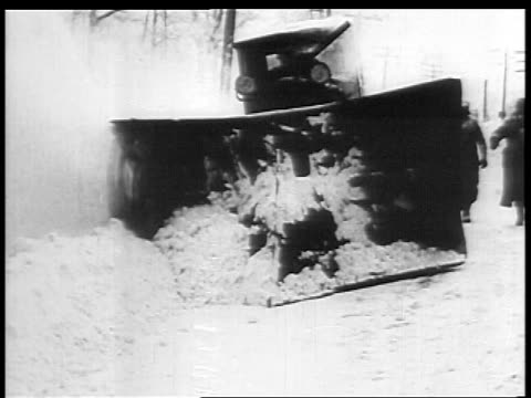 B/W 1927 snow plow shoveling on street in Winter / educational