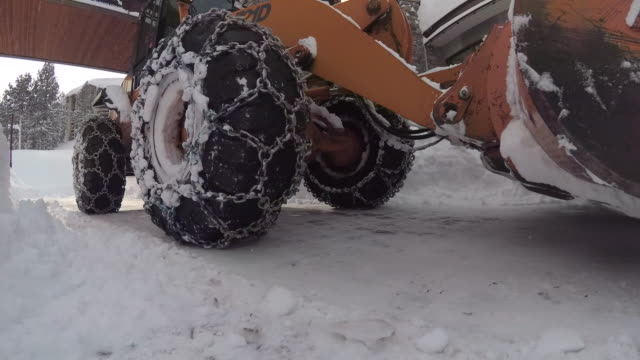 a snow plow tractor with snow chains for traction in the snow and ice. - mammoth lakes video stock e b–roll