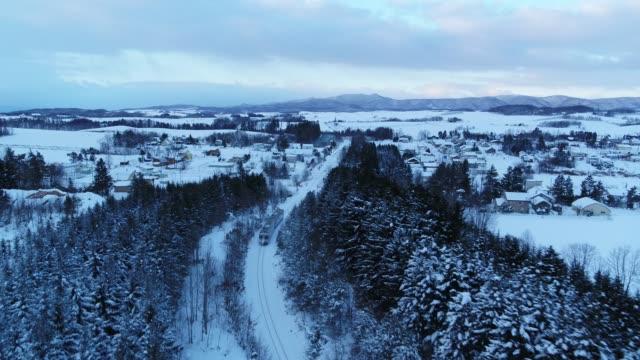 snow scene of a train passing through furano village in sapporo, hokkaido, japan - hokkaido stock videos & royalty-free footage