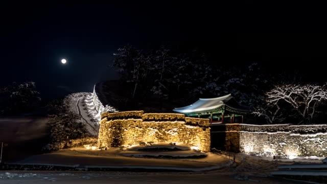 Snow scene of fortified wall in Gochangguneupseong castle(Korea Historic Place 145) with Moon at Night