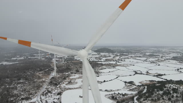 snow scene of oreum (parasitic volcano) and wind turbine on field / jeju-do, south korea - wind turbine stock videos & royalty-free footage