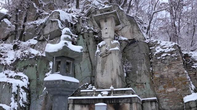 snow scene of seokjobulsang(stone statue of the buddha) and stone lantern at sudeoksa temple - 水の形態点の映像素材/bロール