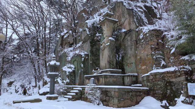 snow scene of seokjobulsang(stone statue of the buddha) at sudeoksa temple - kletterausrüstung stock-videos und b-roll-filmmaterial