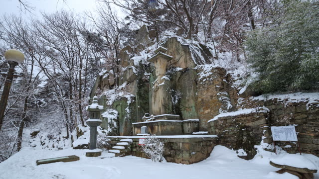 snow scene of seokjobulsang(stone statue of the buddha) at sudeoksa temple - figura maschile video stock e b–roll