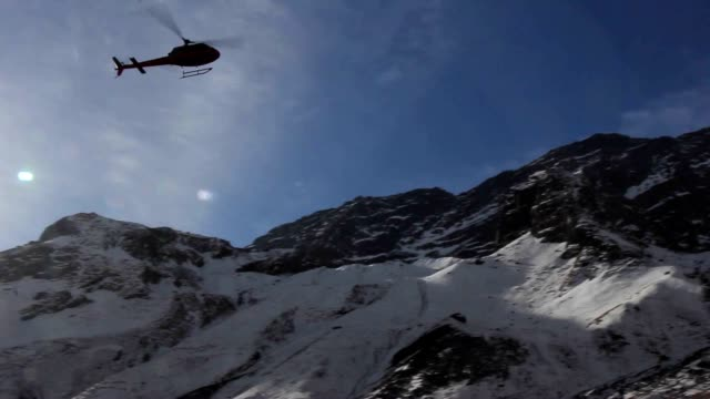 snow scene with flying helicopter in himalayas mountain range - helicopter stock videos and b-roll footage