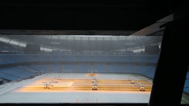 snow shower over the etihad stadium, home of manchester city football cluib, with heat lamps on the pitch. - football pitch stock videos & royalty-free footage