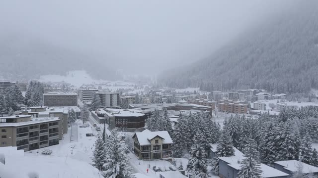 Snow sits on the ground as commercial and residential property stands in Davos Switzerland on Tuesday Jan 12 Mist sits on top of the mountain peak as...