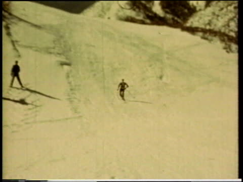 1941 MONTAGE Snow skiers skiing down a hill / United States