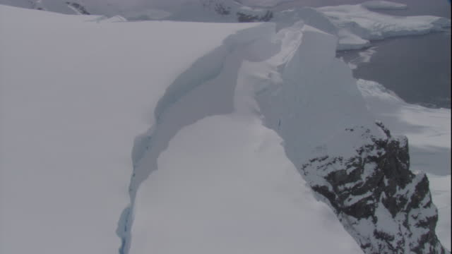 snow splits into several massive chunks on mountain peak on the antarctic coast. available in hd - bbc stock videos and b-roll footage
