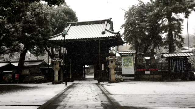 Snow starts to cover a temple in Tokyo Japan as a rare snow storm hits the capital