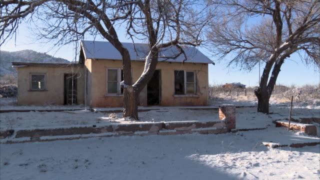 stockvideo's en b-roll-footage met snow surrounds a small abandoned house in rural south dakota. - verlaten slechte staat