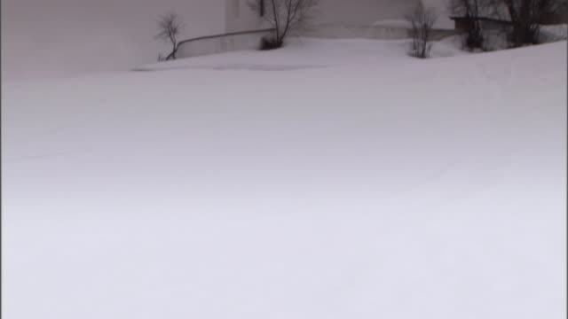 snow surrounds and covers a church. - 尖り屋根点の映像素材/bロール