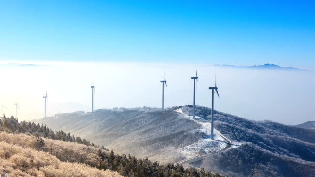 snow view of wind turbine and sea cloud in gangwon province - turbine stock-videos und b-roll-filmmaterial