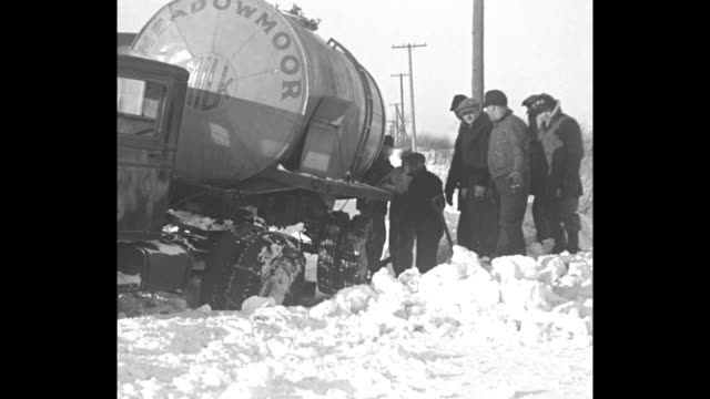 LS snowbank and snowdrifts with telephone poles / several men shovel snow at the side of a road / VS overturned oil tanker from Belleville NJ / VS...