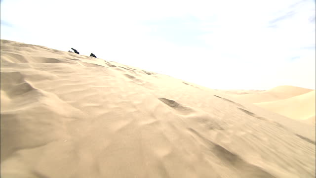 a snowboard rests atop a sand dune. - スノーボード点の映像素材/bロール