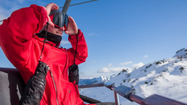 snowboarder adjusting his goggles while riding on chairlift to top of snowcapped mountain - ski goggles stock videos & royalty-free footage