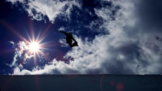 slo-mo-ld-snowboarder in der luft in der half-pipe mit sonne im hintergrund - halfpipe stock-videos und b-roll-filmmaterial
