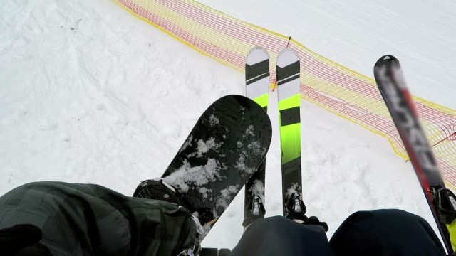 A snowboarder and skiers on a ski lift.