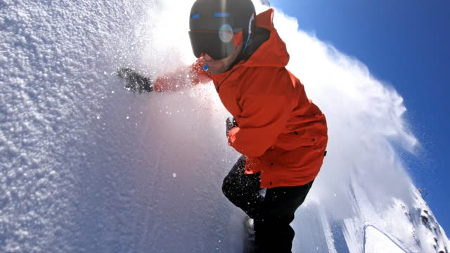 snowboarder carving down the ski slope, leaving a cloud of powder snow behind - snowboard video stock e b–roll