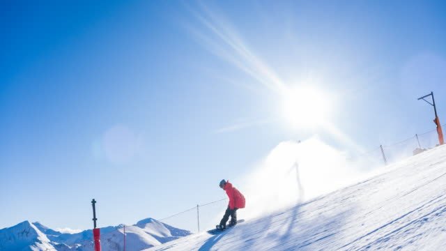 snowboarder carving down the ski slope, leaving a cloud of powder snow behind on a clear sunny day - skiing and snowboarding stock videos and b-roll footage