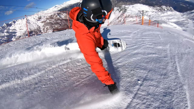 snowboarder carving down the ski slope on a sunny day - winter sport stock videos and b-roll footage