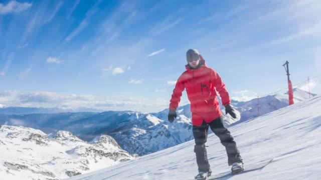 stockvideo's en b-roll-footage met snowboarder snijwerk onderaan de skipiste, spuiten van sneeuw in camera met bergen op achtergrond - skivakantie