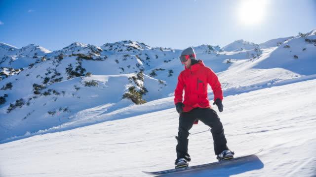 stockvideo's en b-roll-footage met snowboarder snijwerk onderaan de skipiste, spuiten sneeuw, bergen op achtergrond - skivakantie