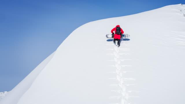 snowboarder auf einen verschneiten berg klettern - snowboardfahren stock-videos und b-roll-filmmaterial
