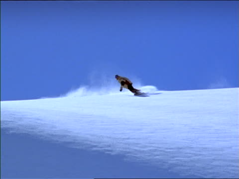 Snowboarder coming down slope / wipes out at bottom