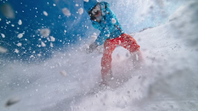 slo mo snowboarder cutting through powder and causing a splash - ski goggles stock videos & royalty-free footage