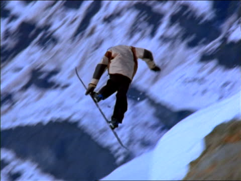 Snowboarder doing jump off cliff + wiping out