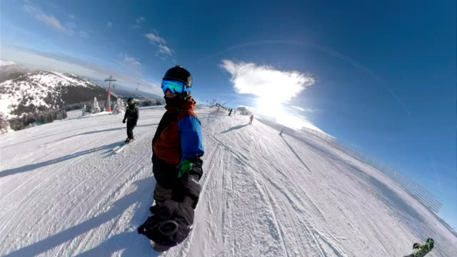 snowboarder enjoying a ride on a sunny mountain holding a monopod - wearable camera stock videos & royalty-free footage