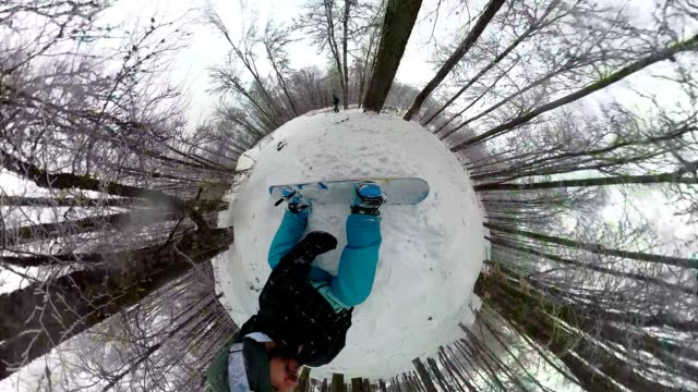 Snowboarder falling while riding in a snowy mountain forest