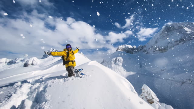 snowboarder full of joy standing on top of snow capped mountain on a sunny winter day - ski holiday stock videos & royalty-free footage