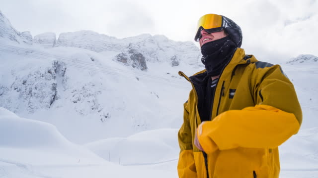 snowboarder macht sich bereit für den abstieg, zückt seine jacke - skibrille stock-videos und b-roll-filmmaterial