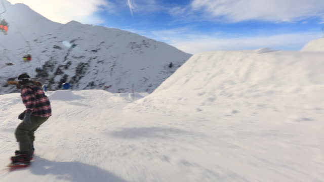 A snowboarder goes through a terrain park at a ski resort and crashes.