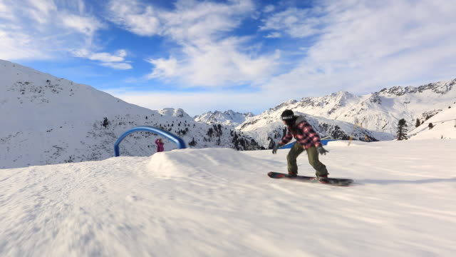 a snowboarder goes through a terrain park at a ski resort. - winter sport stock videos and b-roll footage
