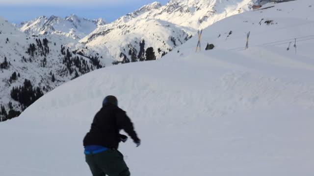 A snowboarder goes through a terrain park at a ski resort.