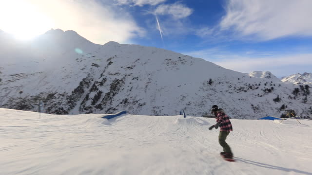 A snowboarder goes through a terrain park at a ski resort.