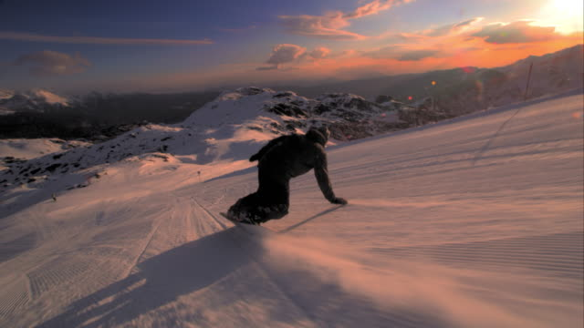 SLO MO TS Snowboarder going down slope spraying snow