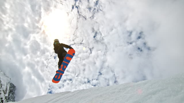 speed ramp snowboarder grabbing his snowboard while jumping in the air - snowboarding stock videos & royalty-free footage